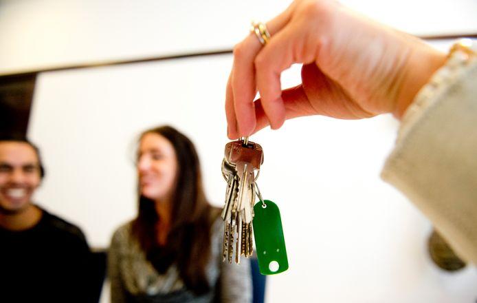 Een stel neemt de sleutels van hun nieuwe huis in ontvangst tijdens de sleuteloverdracht bij de notaris.