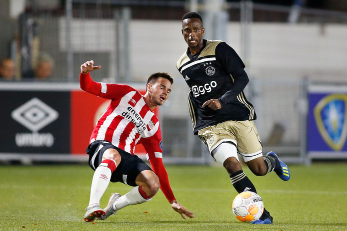 Jong PSV-middenvelder Bertalan Kun wordt gepasseerd door Jong Ajax-speler Dean Solomons.