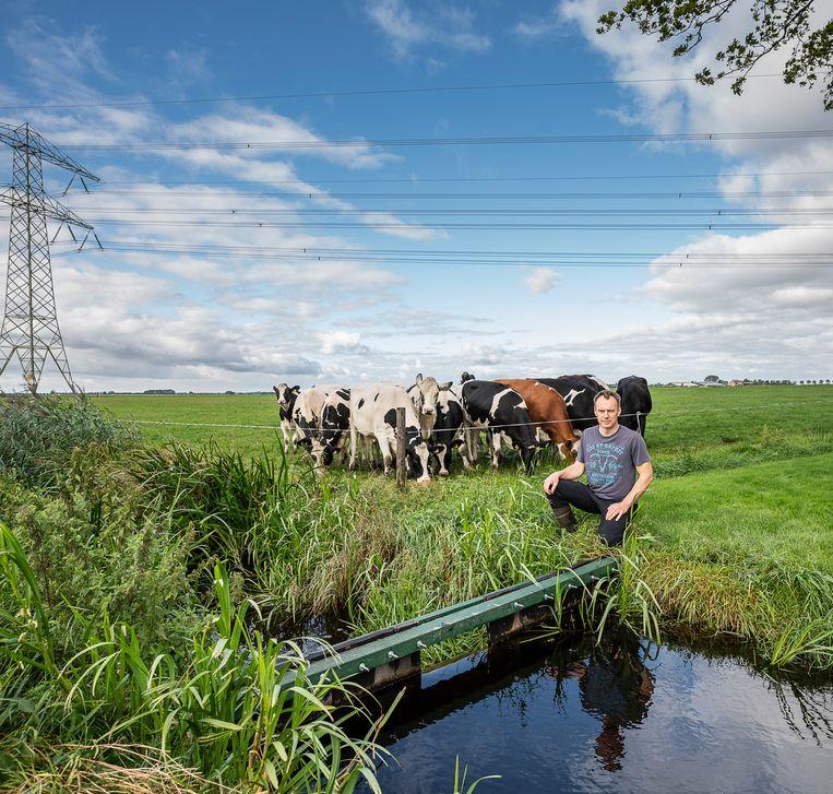 Veehouder Herman Lenes uit Vegelinsoord bij een schutdam die hij in een sloot bij zijn boerderij heeft geplaatst om het waterpeil te reguleren.   Beeld Harry Cock / de Volkskrant