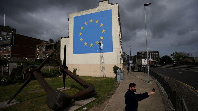 Een man neemt een selfie bij een kunstwerk van Banksy waarop te zien is hoe iemand een 'Britse' ster van de vlag van de Europese Unie verwijdert.