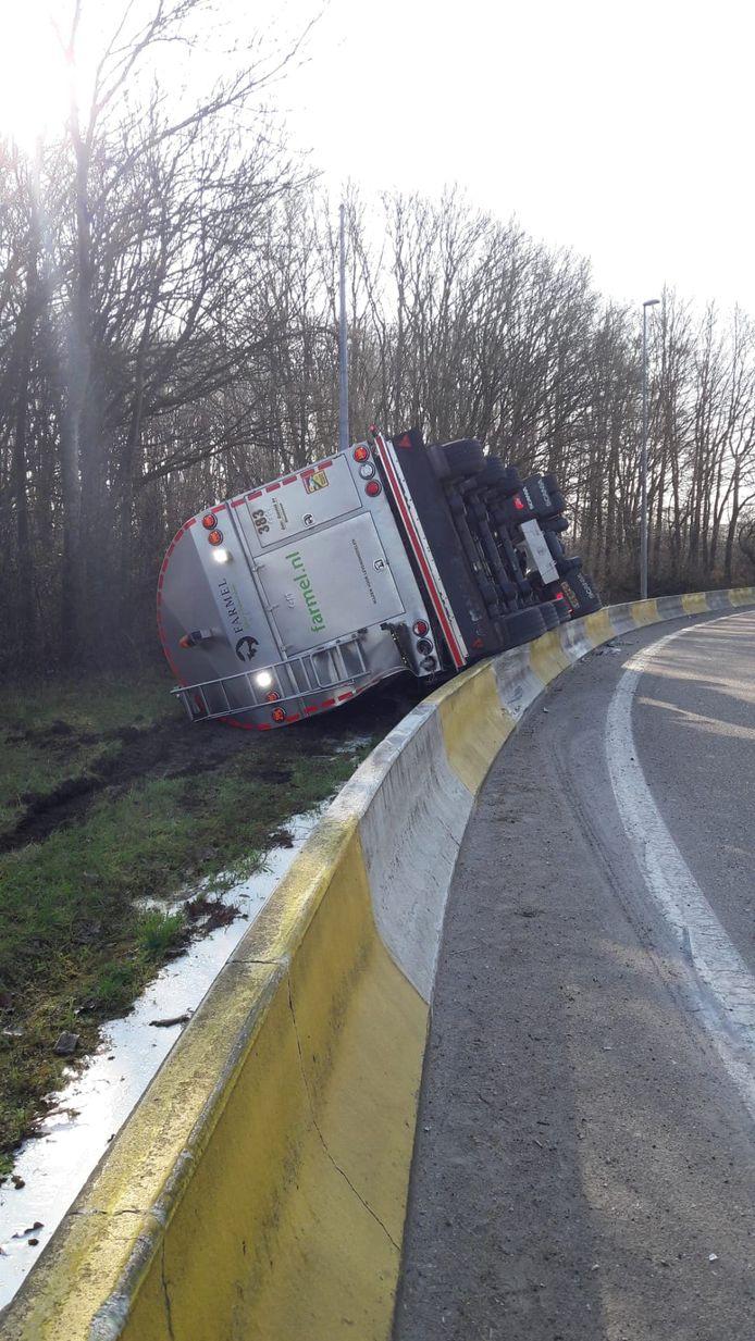 De vrachtwagen kantelde en kwam naast de weg terecht.