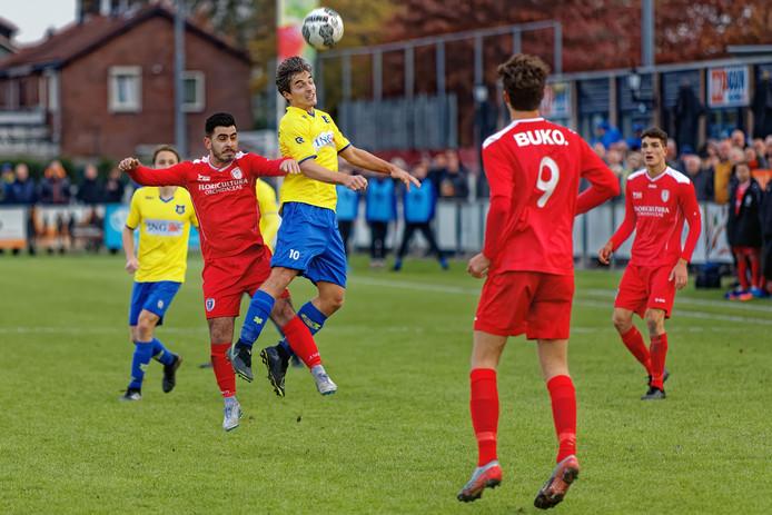 Dongen-speler Tom Wijkmans (midden, gele shirt) wint het kopduel van Cani Yilmaz van ADO'20.