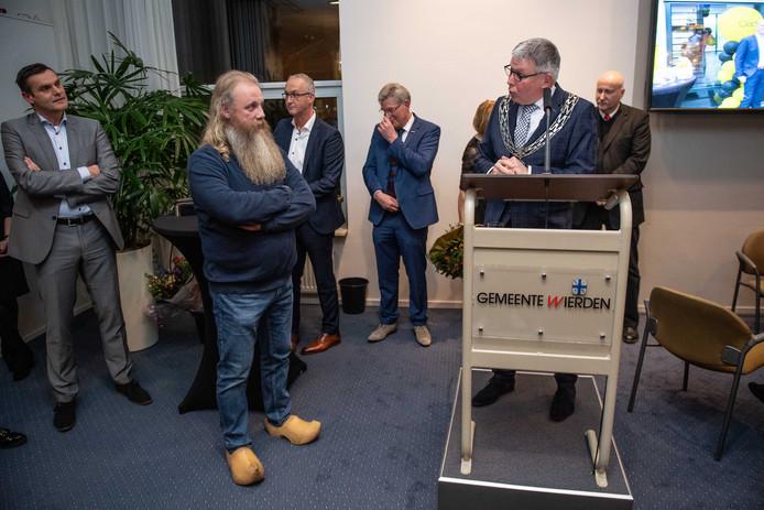 De Enterse klompenmaker Gerald Getkate luistert naar de lovende woorden van burgemeester Henk Robben: ,,U bent een markante man met vaardige handen.''