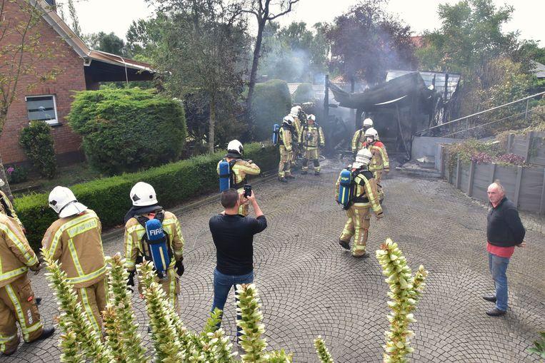 Bewoner Marc Gabriels (rechts) kijkt toe hoe de brandweer het vuur blust.