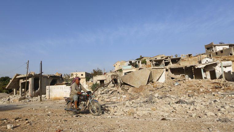 Een man rijdt langs een gebouw dat in puin ligt na een Russische luchtaanval op Latamneh, op het platteland van Hama.