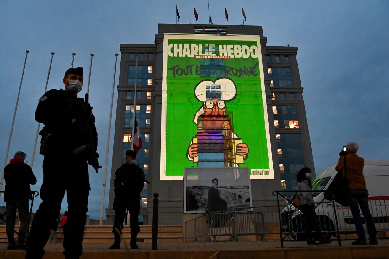Politieagenten in Montpellier bewaken een lokaal regeringsgebouw waarop een cartoon van het satirische tijdschrift Charlie Hebdo wordt geprojecteerd. Beeld AFP