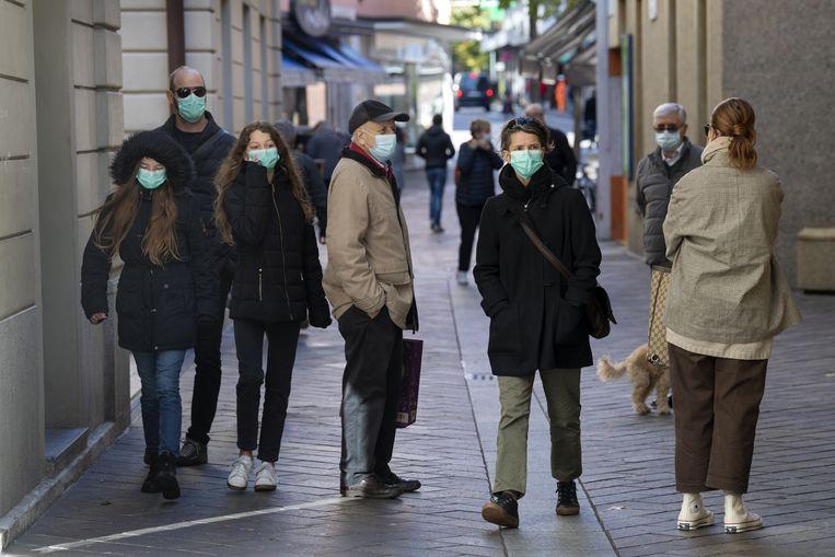 Mensen dragen mondkapjes ter bescherming tegen het coronavirus in Lugano. Beeld EPA