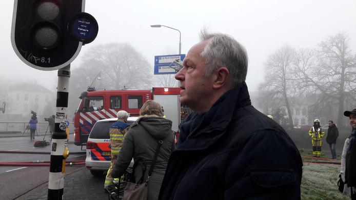 Burgemeester Meijer kijkt toe hoe de brand wordt geblust.