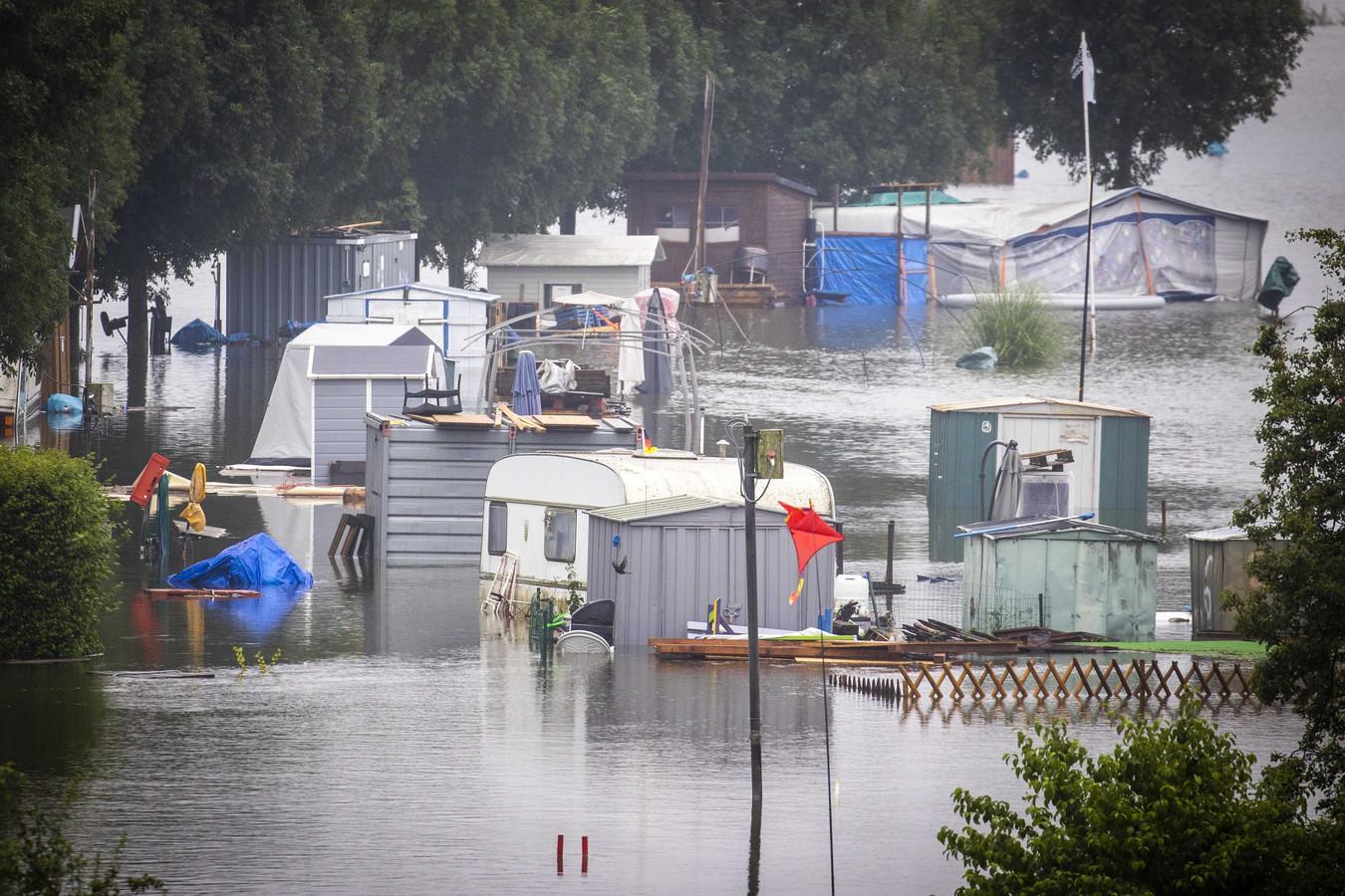 Caravans staan op Camping Hatenboer in het stijgende water in de Maas. Vanwege de hoge waterstand in de rivier ontstaan op veel plekken in Limburg problemen.