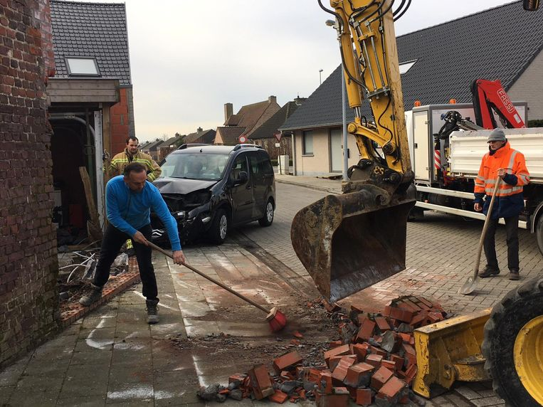 Mannen van de technische dienst ruimen de brokstukken op na de aanrijding waarbij een tuinmuur van twee meter hoog instortte.