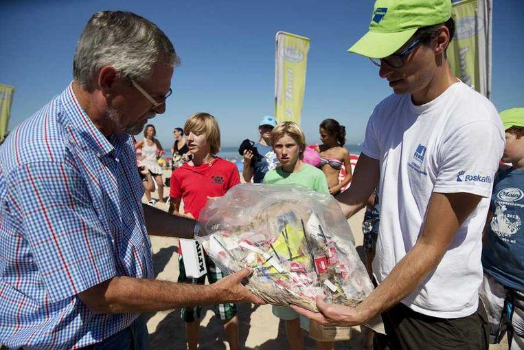 Jeroen Dagevos overhandigt ingezameld afval aan wethouder Peter Ploegaert (L) van de gemeente Sluis op het strand bij Cadzand. Beeld anp