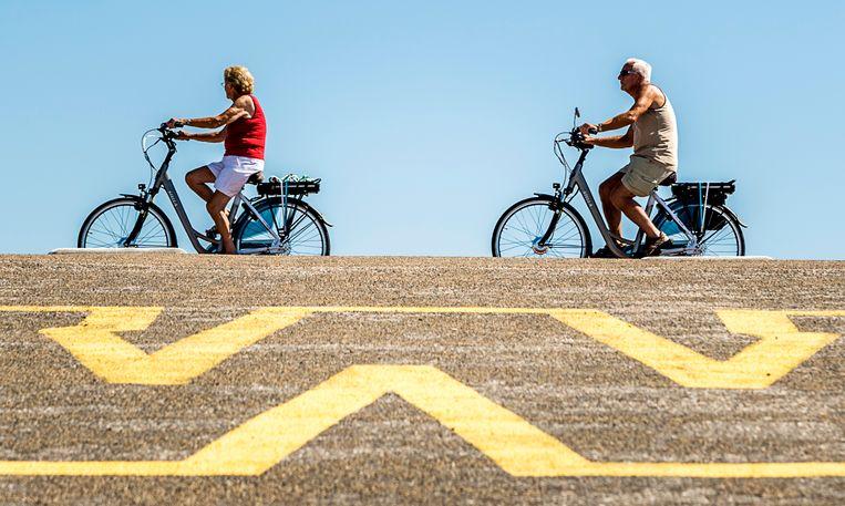 Mensen genieten op hun e-bike van de frisse lucht en het uitzicht op de Brouwersdam.  Beeld ANP, Remko de Waal