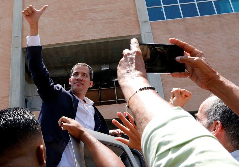 Juan Guaido groet iedereen bij zijn aankomst in Caracas.
