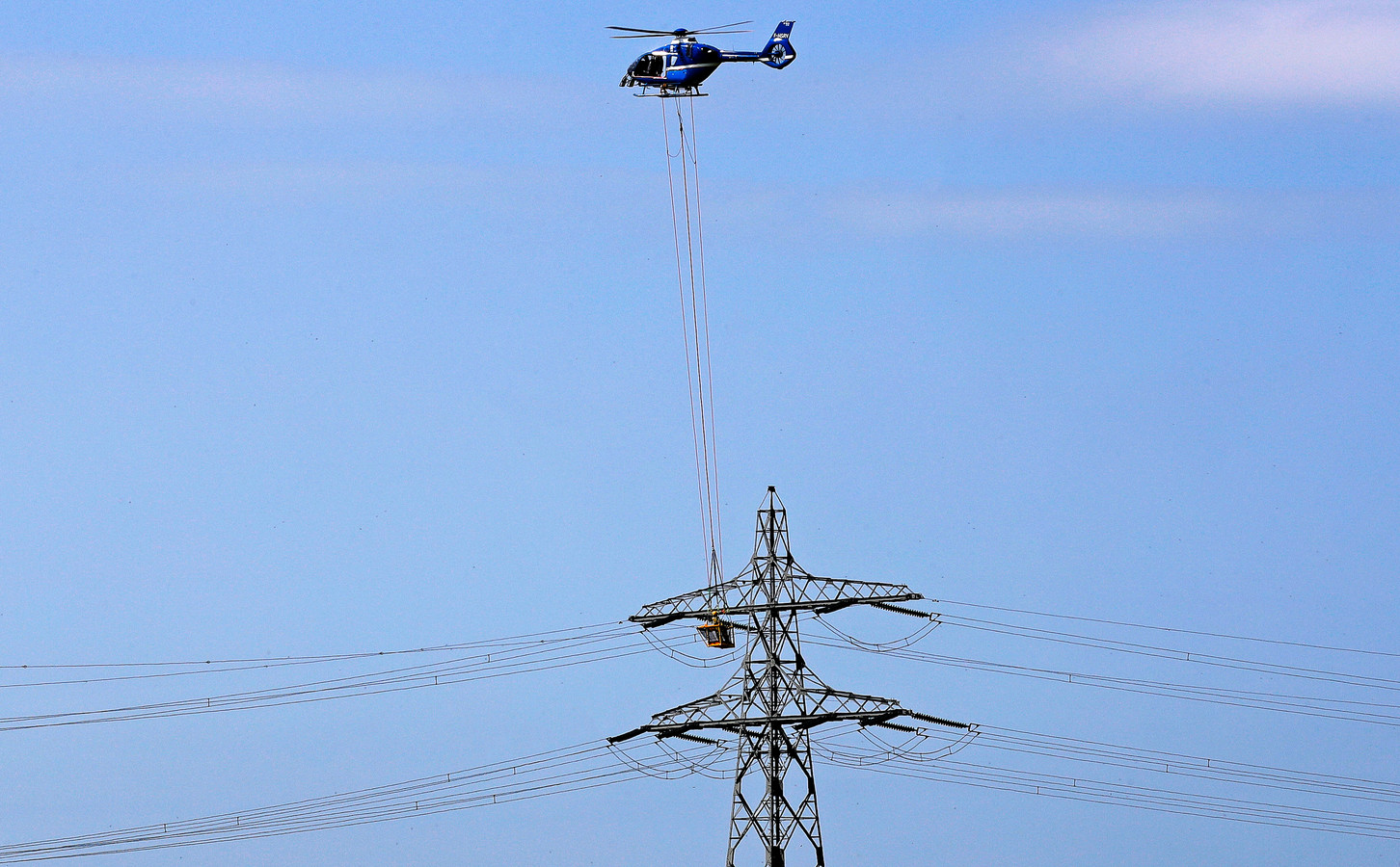 De helikopter hangt boven de hoogspanningsmasten en het bakje met monteurs zit ter hoogte van de stroomdraden.