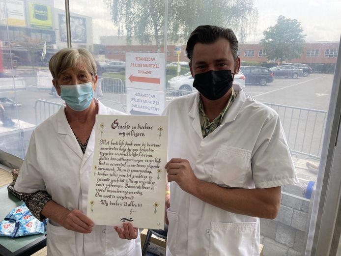 Gepensioneerde Marleen en Moerbeeks gemeentearbeider Andy werken als vrijwilligers in het vaccinatiecentrum. Ze nemen de oorkonde met veel plezier in ontvangst.