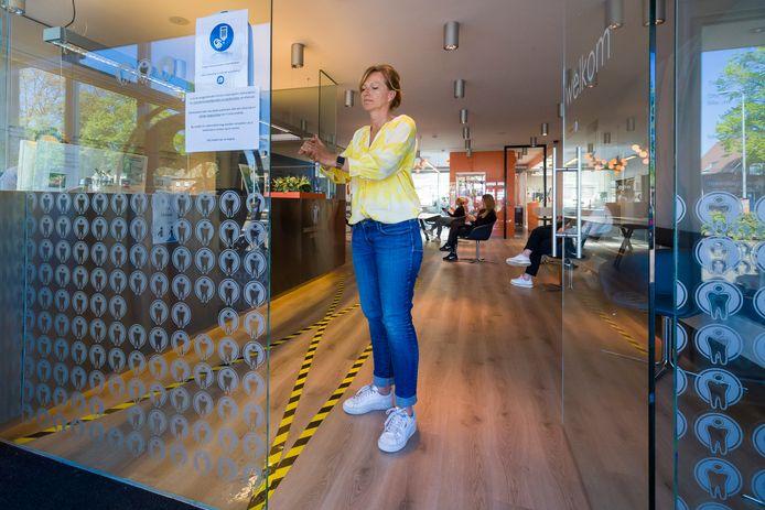 Cindy van Dinther, praktijkmanager van Dents4Friends ontsmet haar handen. De vloer is voorzien van markeringen.