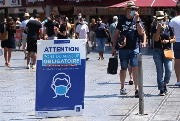 Des personnes marchent près d'une pancarte indiquant que le port du masque est obligatoire dans la zone est photographiée sur la place de la Comédie dans le centre-ville de Montpellier, dans le sud de la France, le 27 juillet 2021, alors qu'une quatrième vague de Covid-19 frappe la France.