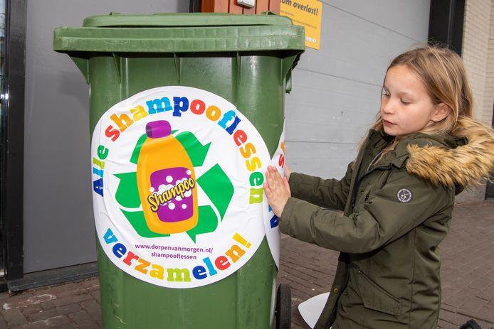 Kinderburgemeester Myla Groenendijk van de gemeente Dalfsen geeft het startsein voor de inzameling van shampooflessen door stickers op kliko's te plakken.