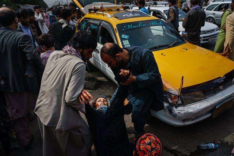 Afghaanse mannen helpen een gewonde vrouw recht. Aan de luchthaven in Kaboel proberen de taliban de menigte met harde hand onder controle te houden.  Beeld Photo News