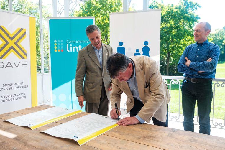 Burgemeester Debrabandere tekent het document.