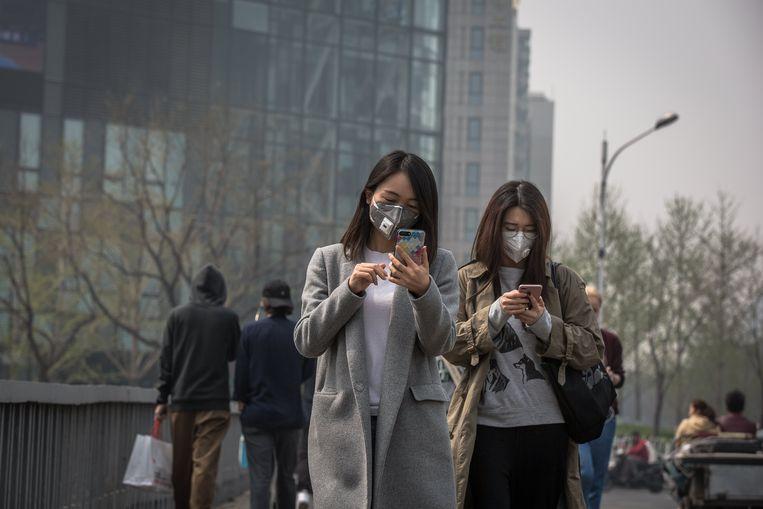 Vrouwen dragen beschermende maskers tijdens een slechte dag begin vorige maand in Peking, China. Beeld EPA