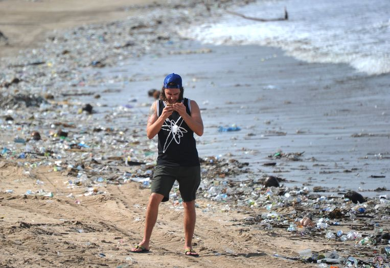 A tourist stands between plastic rubbish at Kuta beach near Denpasar, on Indonesia's tourist island of Bali on December 19, 2017. The palm-fringed shoreline of Bali's Kuta beach has long been a favourite with tourists seeking sun and surf, but nowadays its golden shores are being lost under a mountain of garbage. / AFP PHOTO / SONNY TUMBELAKA / TO GO WITH Indonesia-rubbish-Bali-environment,FEATURE by Bagus Saragih Beeld AFP