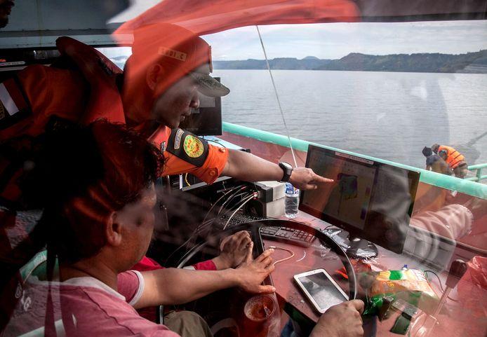 Reddingswerkers kijken op een monitor naar sonarbeelden van de gezonken veerboot