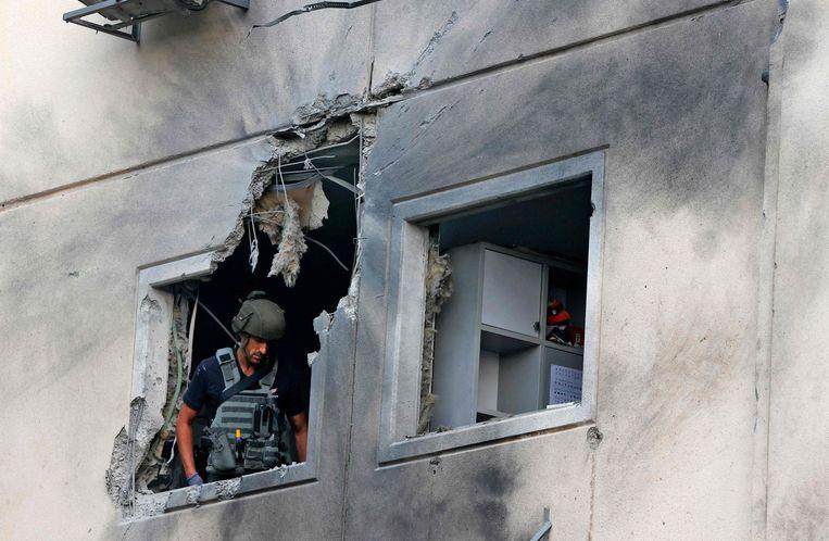 Een Israëlische militair controleert een beschadigd appartement in de stad Ashkelon, nadat raketten werden afgevuurd vanuit de Gazastrook. Beeld AFP