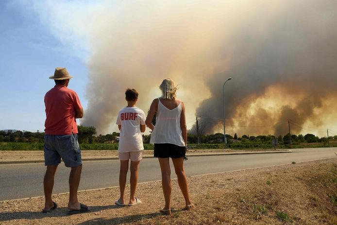 Mensen kijken langs de kant van de weg naar de branden ten noorden van Grimaud.