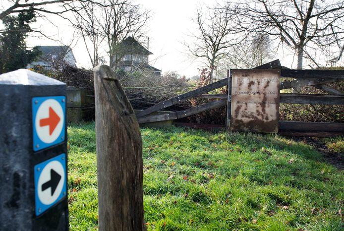 De bordjes wijzen in Erichem nog de boomgaard in, maar op het hek is te lezen dat klompenwandelaars er niet meer welkom zijn.