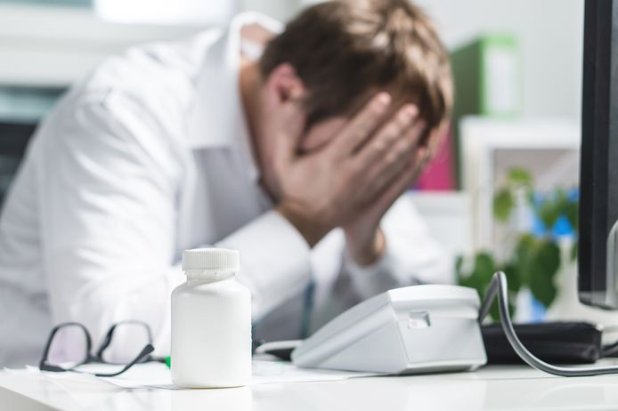 Stressed doctor cover face under pressure. Sad nurse, tired physician or upset doc. Medic crying in hospital office. Malpractice, treatment error and mistake or negligence. Workplace bullying.