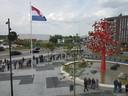 Plein voor nieuwe gerechtsgebouw in Breda. De koning komt daar zometeen aan om het nieuwe gebouw te openen. Het plein stroomt langzaam vol met publiek.