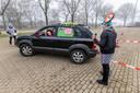 Bij de start van de rit op het parkeerterrein van het sportpark moeten deelnemers achteruit inparkeren. Alain van Gool en Nancy Voestermans kijken of het goed gaat.