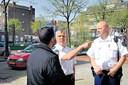Wijkagenten Menno Tibout (links) en Sander Boer in gesprek met een buurtbewoner op het Frederiksplein
