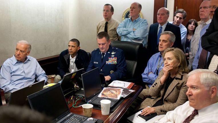 Obama in jasje volgt geconcentreerd de bewegingen van de elitesoldaten en Clinton houdt gespannen een hand voor haar mond. Beeld AFP