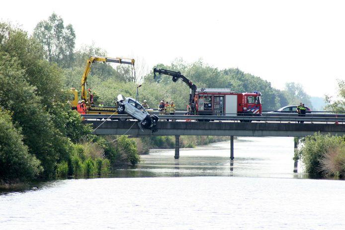 De auto wordt uit het water langs de A6 getakeld.