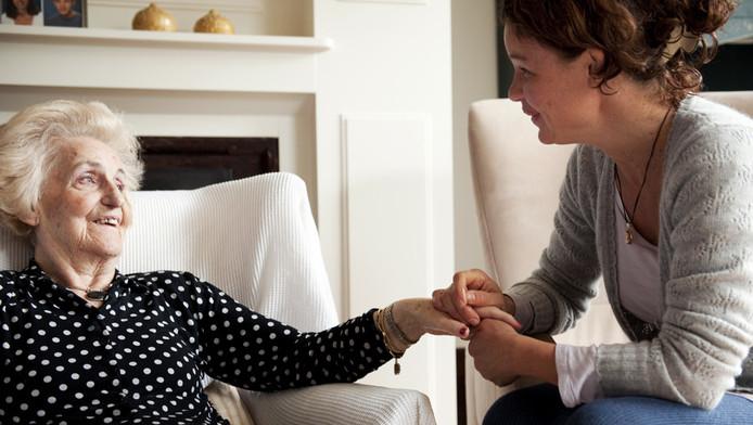 Een medewerkster van Evita Zorg in Den Haag biedt hulp aan een oudere dame.
