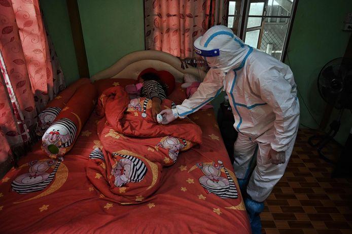 Een gezondheidswerker checkt de zuurstofwaarde in het bloed bij een patiënt in de omgeving van Bangkok.