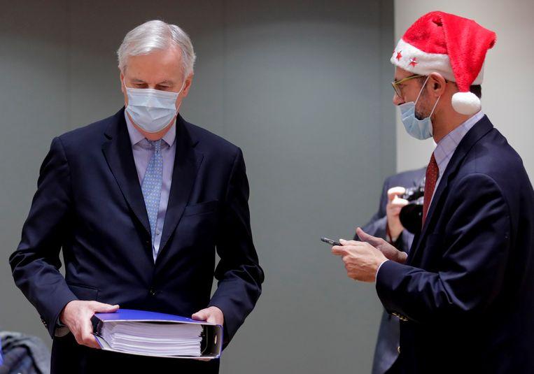 EU-brexit-onderhandelaar Michel Barnier (zonder kerstmuts) presenteerde het 1246 pagina's tellende handelsakkoord op Eerste Kerstdag aan de 27 EU-ambassadeurs in Brussel. Rechts, met kerstmuts, een medewerker.  Beeld AP