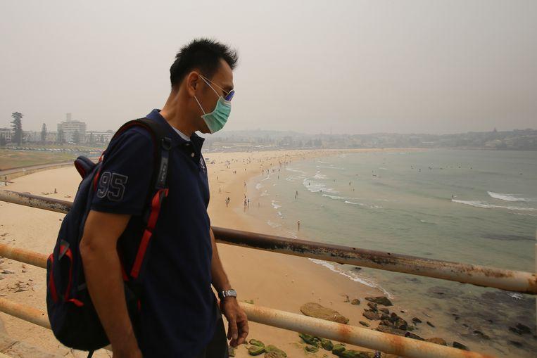 Een man loopt voorbij Bondi Beach in Sydney. De stad gaat gebukt onder een deken van rook en as afkomstig van de bosbranden. Beeld EPA