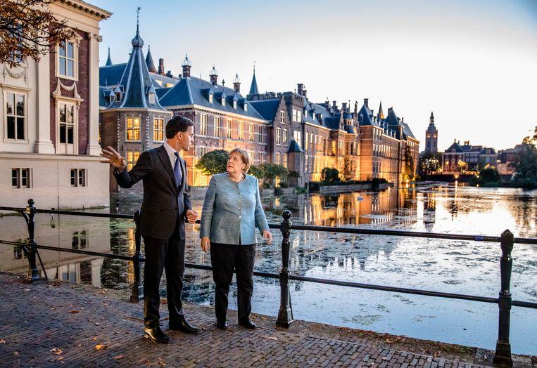 Minister-president Mark Rutte en  bondskanselier Angela Merkel lopen langs de Hofvijver. Beeld Hollandse Hoogte /  ANP