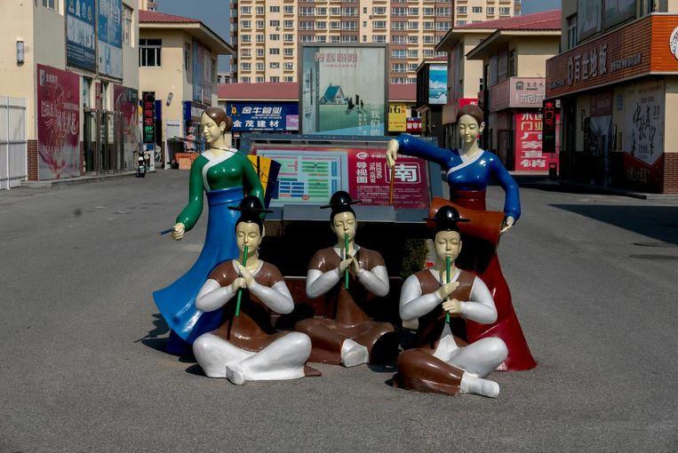 Traditionele Koreaanse figuren luisteren deze vers uit de grond gestampte wijk op. Beeld Zhang Peng, Getty Images