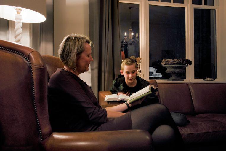 Moeder Ellen van Veen en jongste zoon Nathan lezen de Bijbel. Beeld Otto Snoek