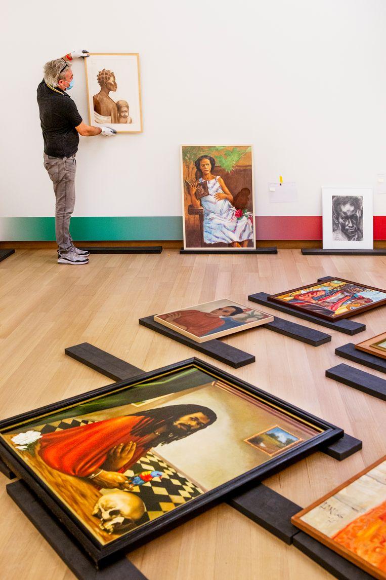 Opbouw van de tentoonstelling Surinaamse school in het Stedelijk Museum in Amsterdam. Met vooraan op de grond het zelfportret van Cliff San A Jong. Beeld Pauline Marie Niks