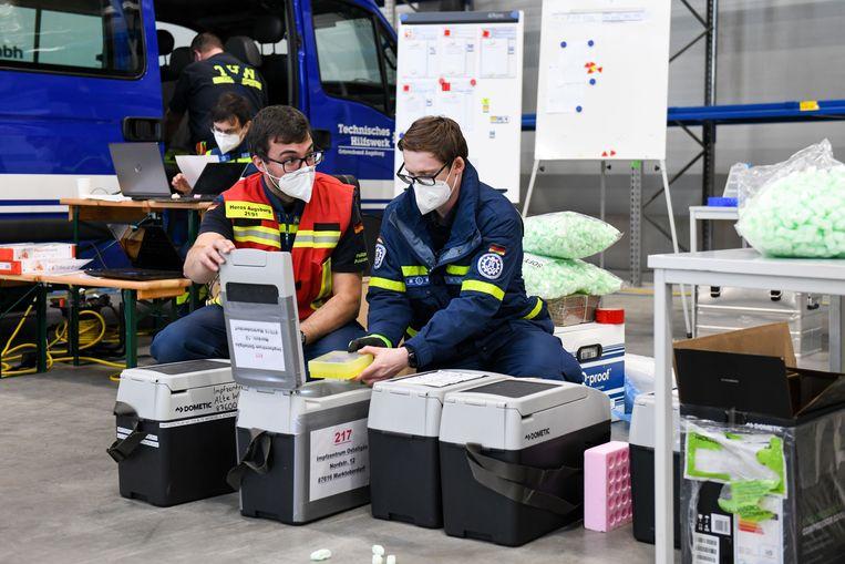 Flesjes van het BioNTech/Pfizer vaccin worden in verkoelende transportdozen verpakt.  Beeld Tobias Hase/dpa
