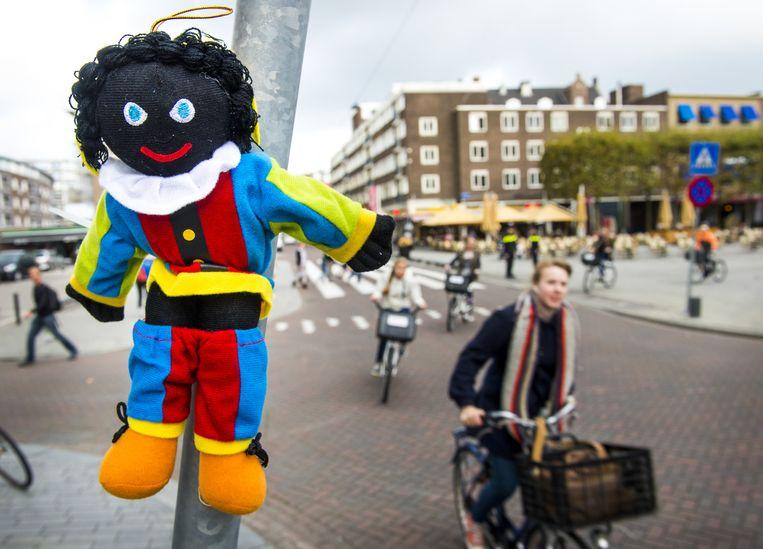 Aan de Meent hangt een klein zwart pietje aan een lantaarnpaal. Leefbaar Rotterdam heeft verspreid over de stad 300 poppetjes opgehangen, met als boodschap 'Wij willen blijven'. Beeld anp