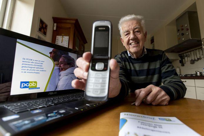 Henk Markerink - mét 'klap-mobiel' - bij zijn laptop aan de keukentafel. Hij stopt na 10 jaar als voorzitter van ouderenbond PCOB in Neede, maar gaat door als belangenbehartiger ouderenzaken.
