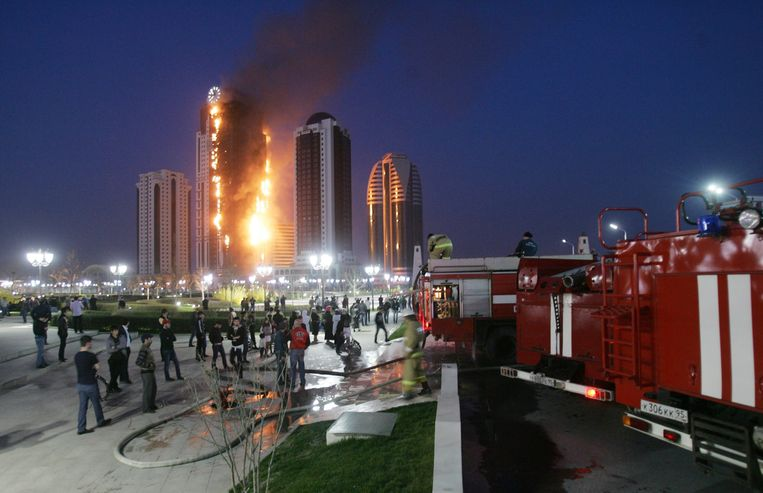 epa03648940 Residents and firefighters watch flames rising from the burning 'Grozny City'  luxury apartment tower in Grozny, Chechen Republic, Russia, 03 April 2013. Reporte state that the Head of the Chechen Republic presented French actor Gerard Depardiue with an apartment in the 40-floor building.  EPA/KAZBEK VAKHAYEV Beeld null