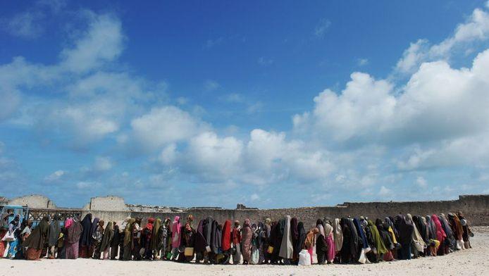 Vrouwen in een vluchtelingenkamp bij Mogadishu staan in de rij voor voedsel.