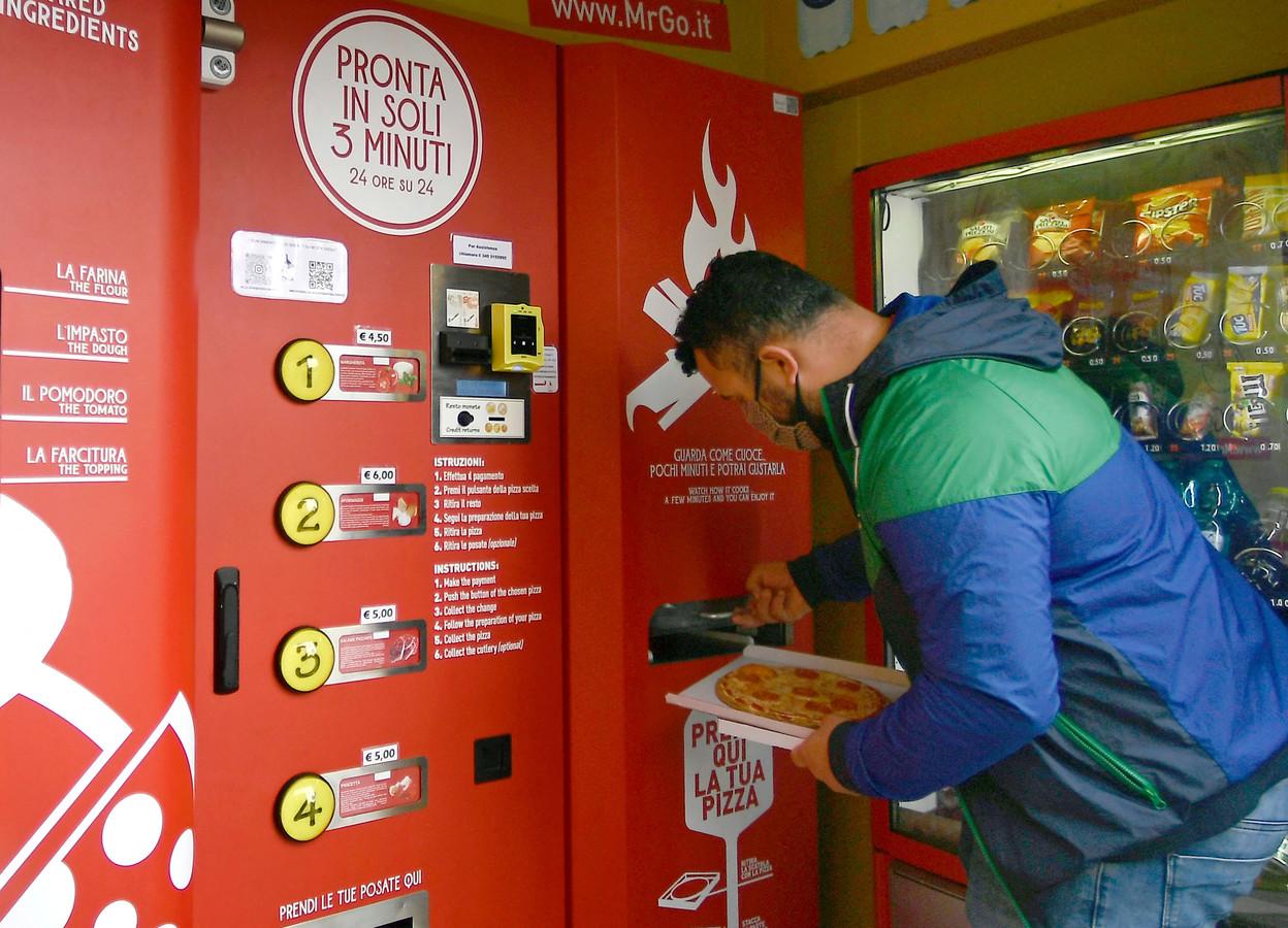 Een Italiaan haalt in Rome de allereerste uit een pizza-automaat.
